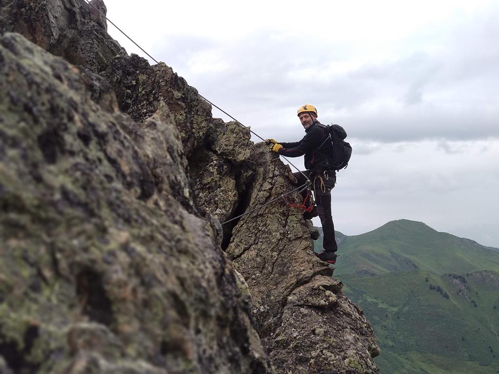 mężczyzna wchodzący po via ferracie na szczyt