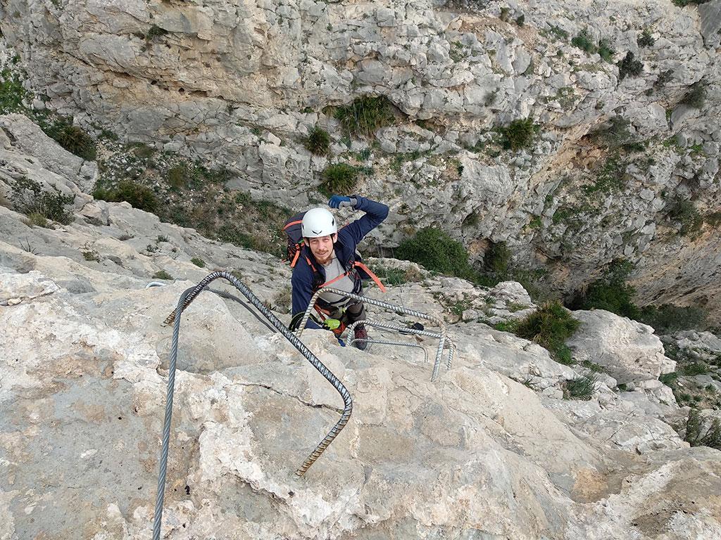widok z góry na człowieka w kasku stojącego na metalowej klamrze wystającej ze skały, lewą rękę ma zgiętą w łokciu i uniesioną prawą trzyma się jednej z klamer