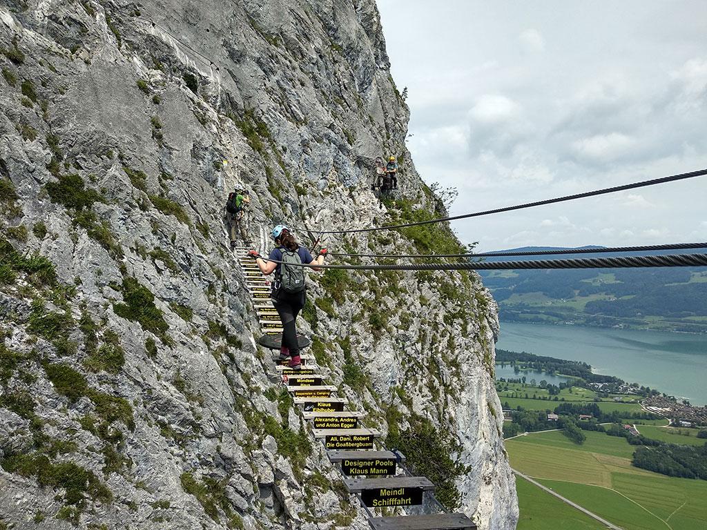 na pierwszym planie stojąca tyłem kobieta przechodząca przez most linowy z deseczkami pod nogami i stalowymi linami w formie poręczy; na dalszym planie dwie osoby jedna schodzi z mostka, druga odpoczywa na skale