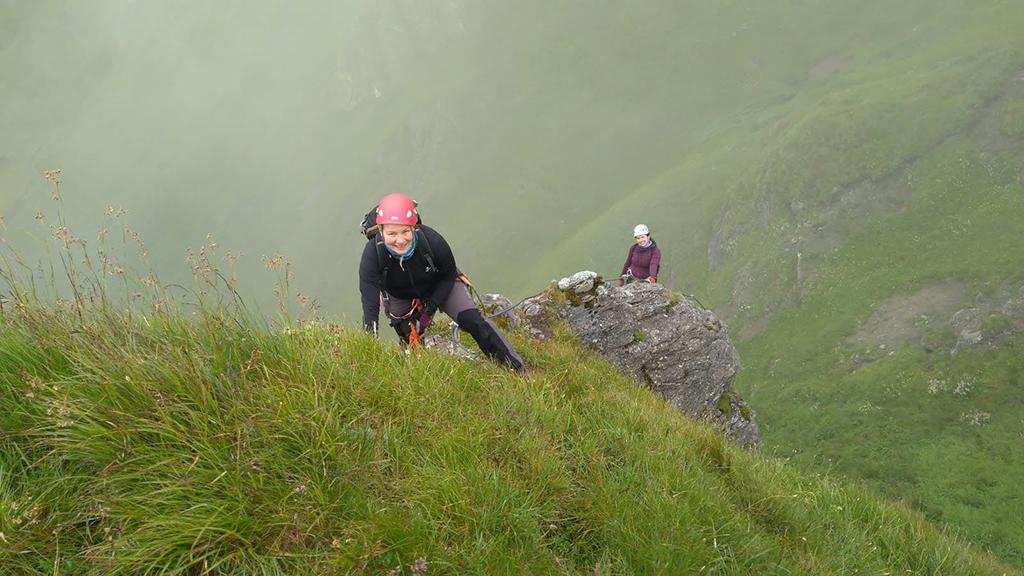 dwie kobiety, jedna bliżej, druga z tyłu - stoją niżej niż fotografujący, znajdują się na tle zielonej trawy