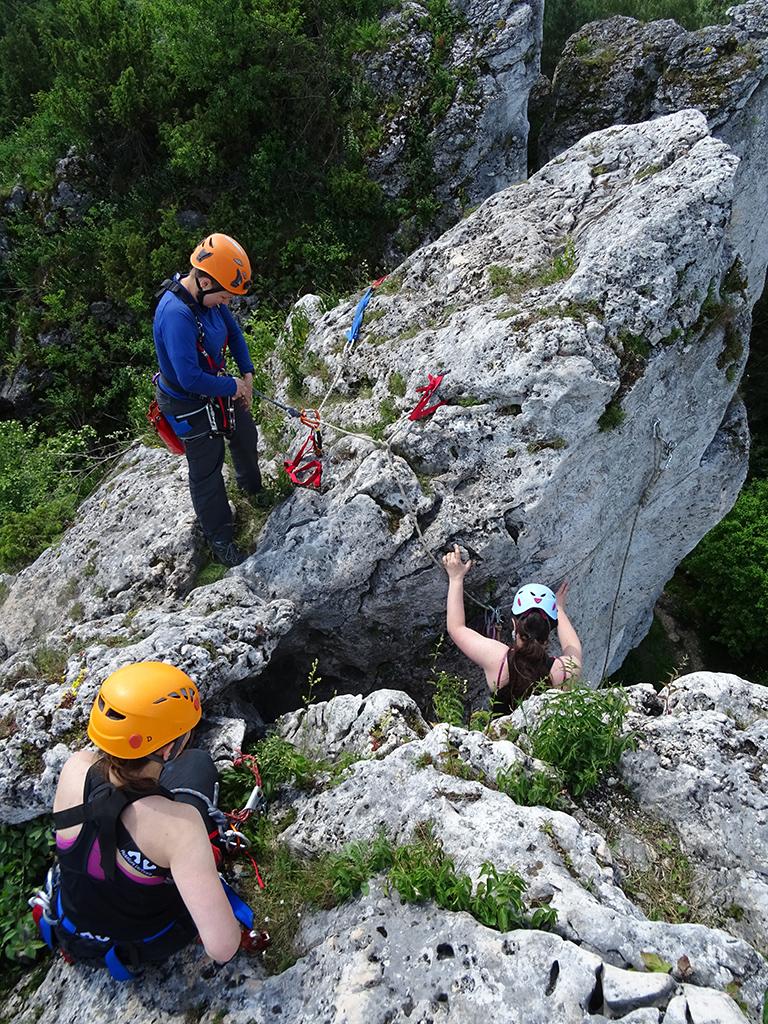 trzy kobiety na szczycie ostańca skalnego, jedna przechodzi trawers w dół, jedna przygotowuje się do zejścia, jedna siedzi na skale