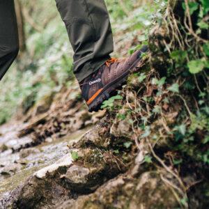 mężczyzna w butach GORE-TEX przechodzi przez strumień