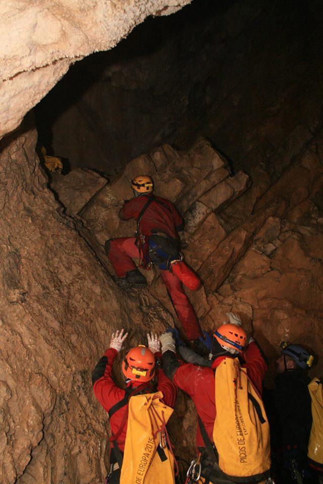 jeden grotołaz wspinający prożek Rabka w jaskini czarnej, na dole dwóch innych grotołazów asekuruje go z uniesionymi rękami
