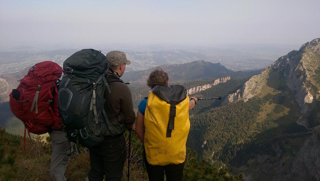 trzy stojące osoby, dwie z lewej mają duże plecaki, osoba po prawej stronie ma worek jaskiniowy, w prawej ręce trzyma kijek trekkingowy, którym wskazuje przed siebie