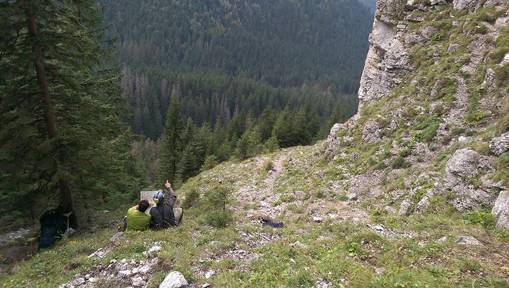 dwie postaci siedzące tyłem, w ręku trzymają mapę, jedna z osób wskazuje przed siebie prawą ręką