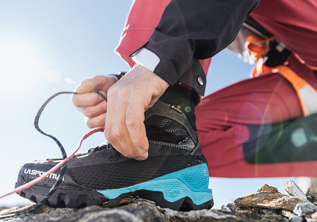 Wysoki but trekkingowy La Sportiva na pierwszym planie oraz dłonie mężczyzny wiążącego sznurówki.