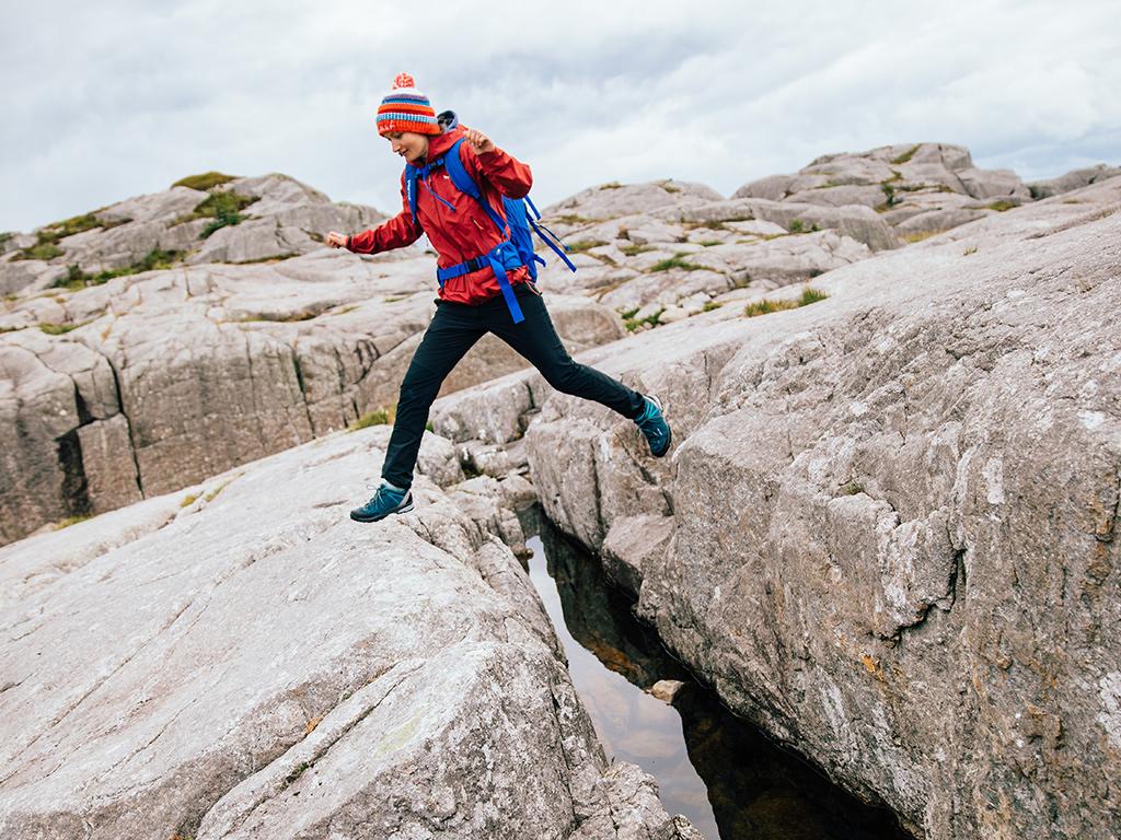 Kobieta w niskich butach trekkingowych skacząca przez skalną szczelinę wypełnioną wodą