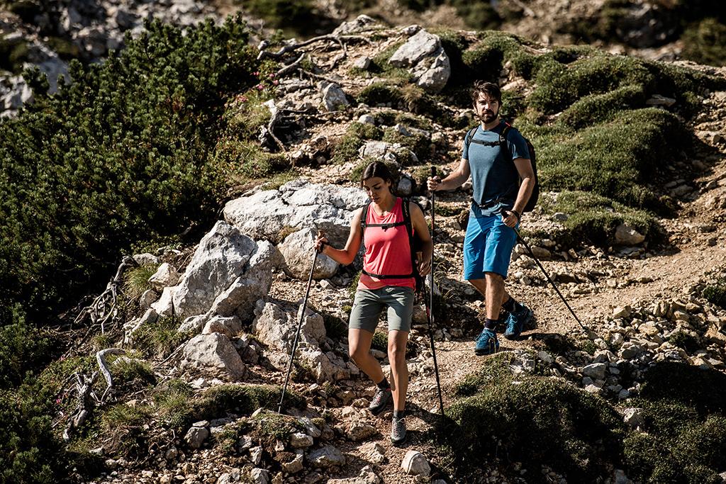 Dwoje turystów, którzy schodzą z gór. Mają na sobie koszulki, szorty i niskie buty trekkingowe, a w rękach kije trekkingowe.