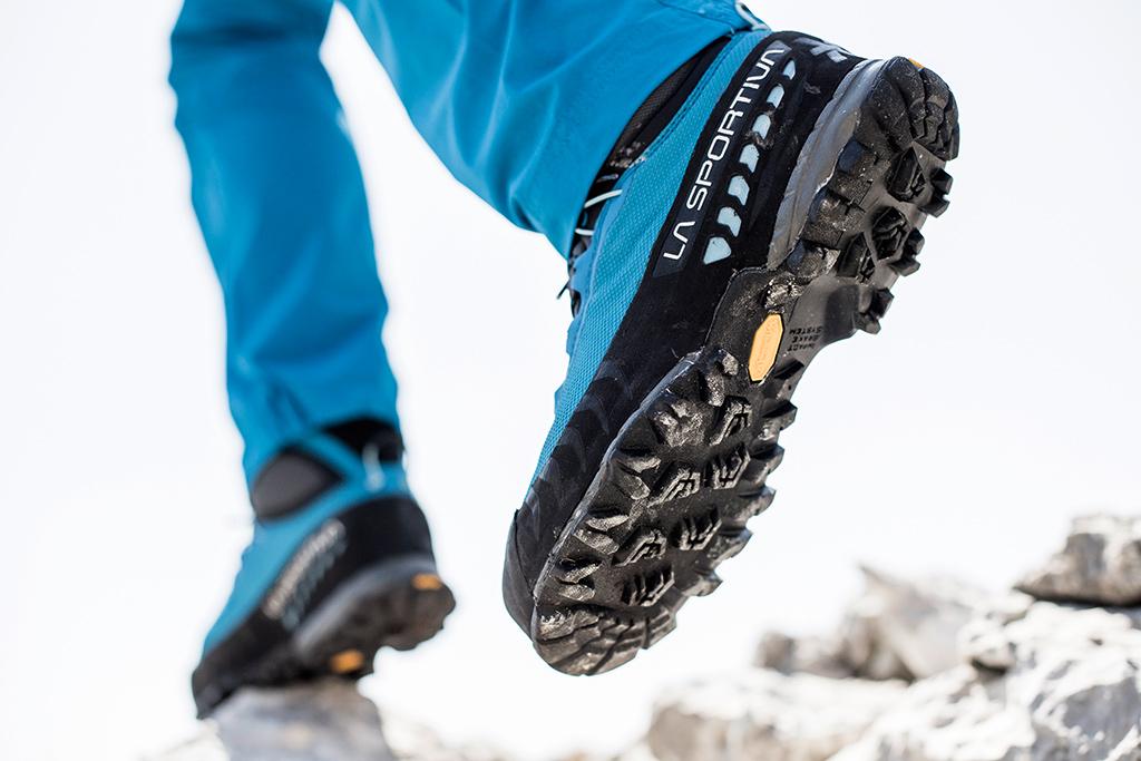 Damskie buty trekkingowe w akcji - zbliżenie na podeszwę Vibram. Nogi w niebieskich spodniach oraz wysokie buty w góry o niebieskiej cholewe
