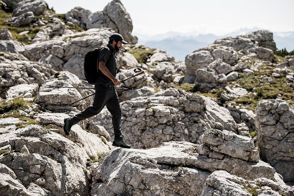 Schodzący z góry mężczyzna w butach z gumowym otokiem, chroniącym przed uszkodzeniami przez skalne podłoże