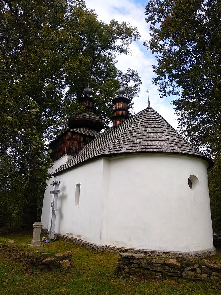 biała cerkiew z dachem krytym gontem - zdjęcie od strony absydy