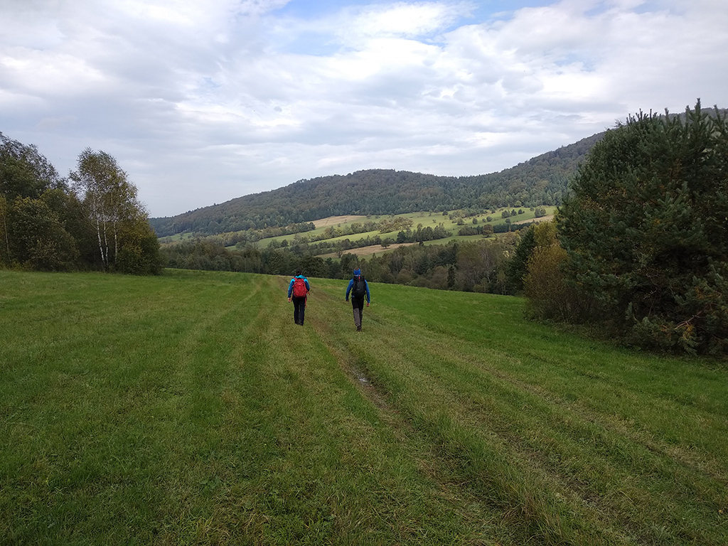 dwie postaci na polach wśród gór