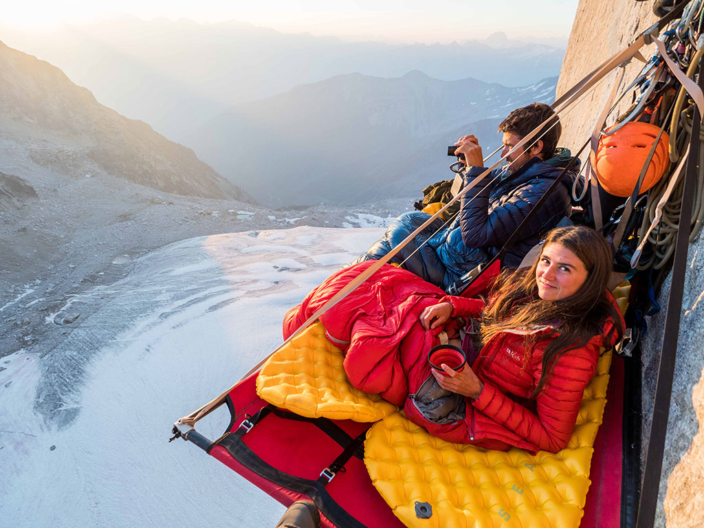 para siedząca na specjalnej platformie portaledge zawieszonej na skale, kobieta patrzy w aparat, mężczyzna na drugim planie robi zdjęcie widokom