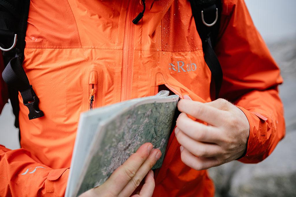 człowiek wkładający złożoną mapę do kieszeni piersiowej w kurtce przeciwdeszczowej