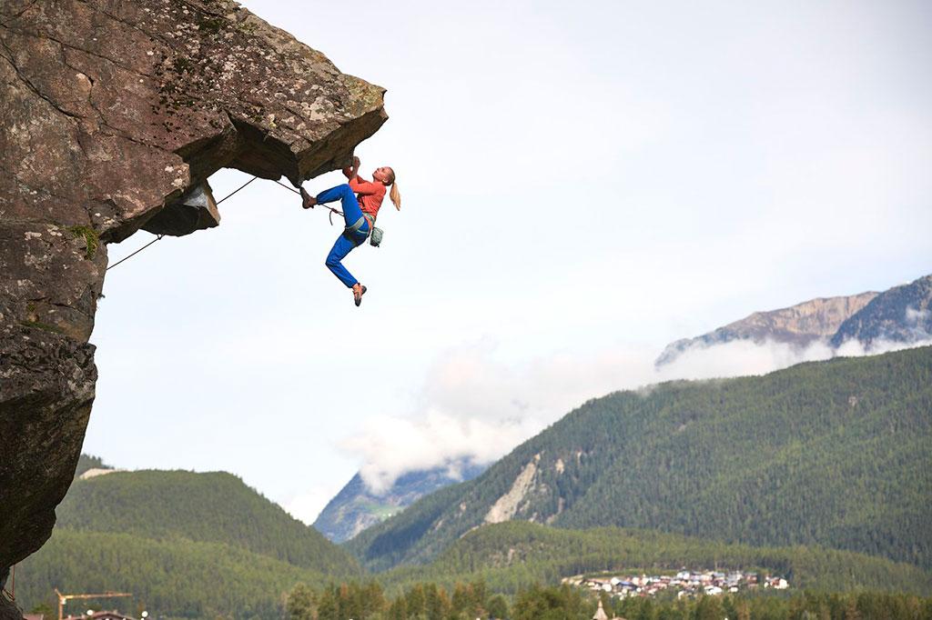 kobieta wspinająca się pod skalnym okapem w tle widoczne góry