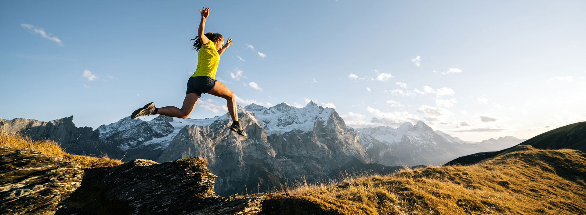osoba skacząca przez rów w tle góry