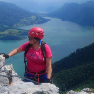 ferrata drachenwand na pierwszym planie skała i lina stalowa, pośrodku kobieta w kasku i uprzęży, w tle widać jezioro i sąsiednie góry