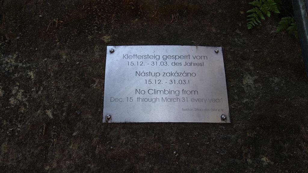 tabliczka przytwierdzona do skały z napisami w j. niemieckim, czeskim i angielskim informującym o zakazie wejścia w okresie od 15 grudnia do 31 marca każdego roku