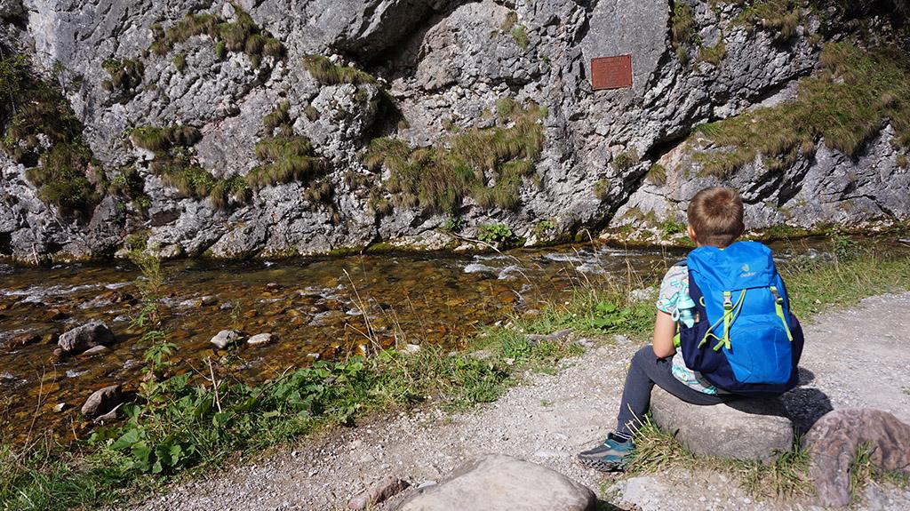 chłopiec z niebieskim plecakiem siedzi na kamieniu tuż nad potokiem