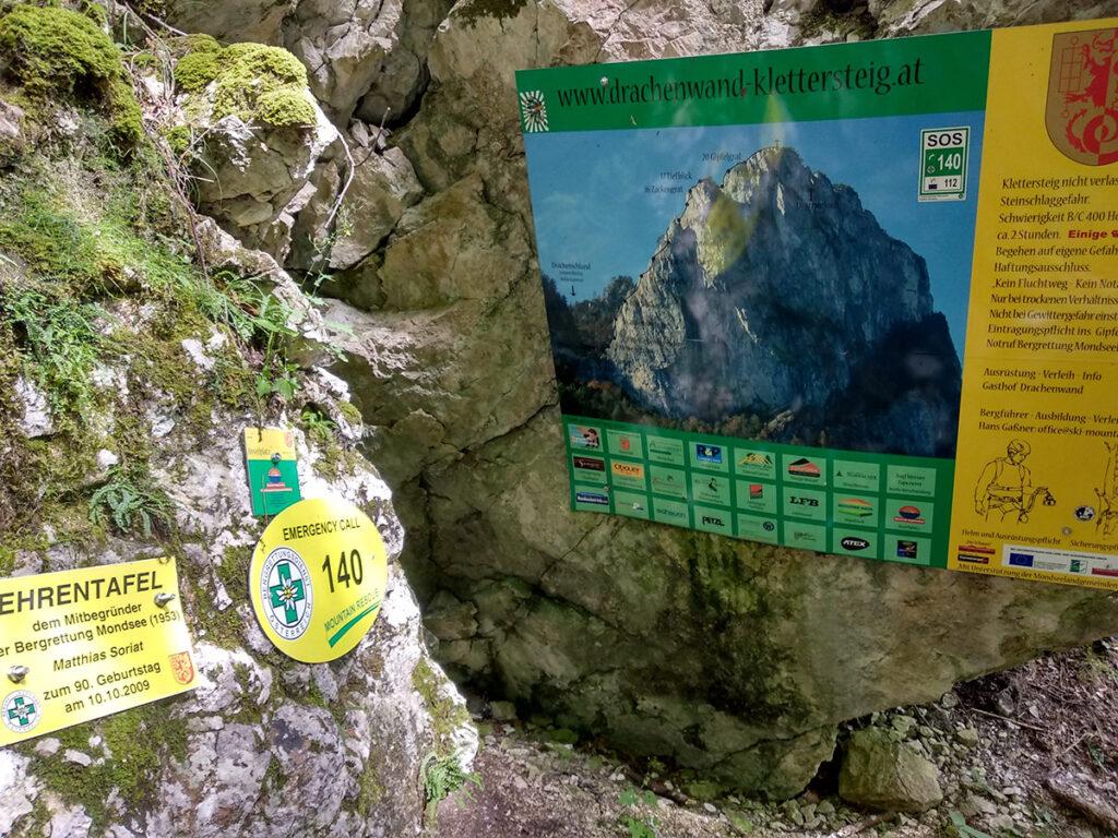 tablice informacyjne, w tym zawierające numer alarmowy, przed wejściem na via ferratę Drachenwand