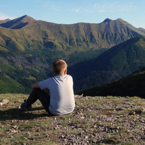 chłopiec siedzi tyłem i patrzy na panoramę tatr zachodnich