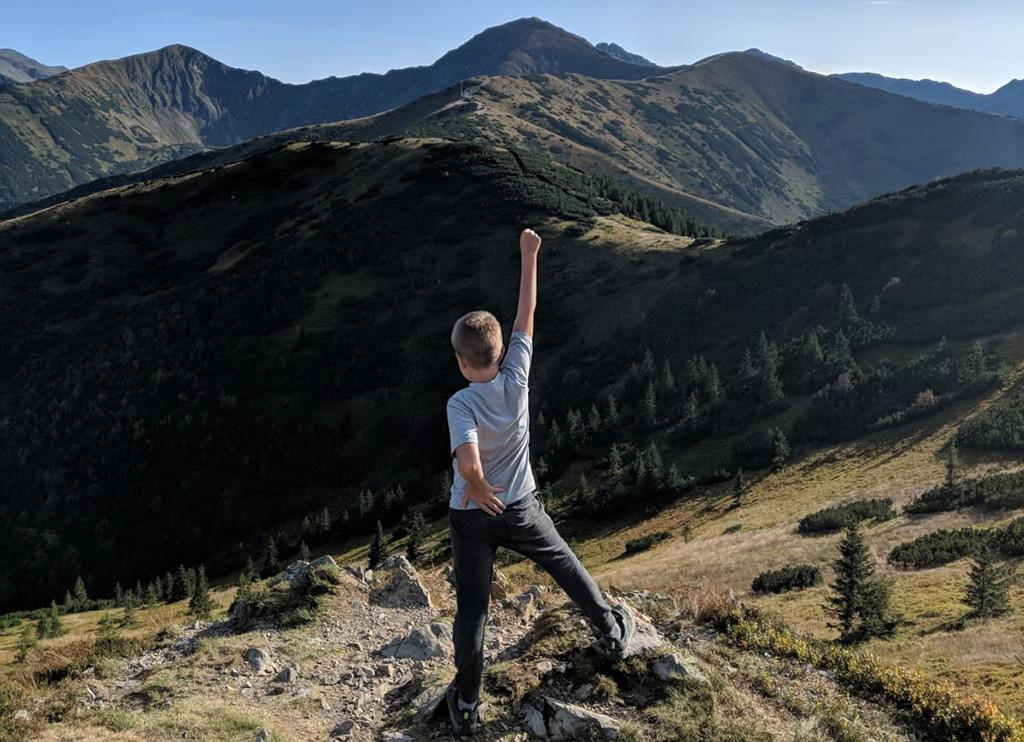 na pierwszym planie stojący chłopiec ma uniesioną prawą rękę, a lewą się podpiera pod bok w tle widoczne szczyty gór