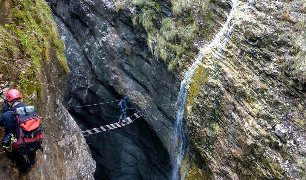 na pierwszym planie osoba z plecakiem poruszająca się po klamrach na skale, w głębi druga osoba przechodząca przez mostek w kanionie