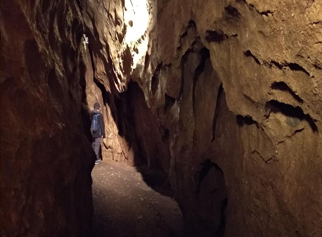 szczelina w jaskini na górze widać światło, na dalszym planie stoi chłopiec z plecakiem